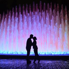 Romantic kiss in front of a lighted fountain