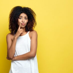 Woman thinking - unconvinced - Standing in front of yellow wall